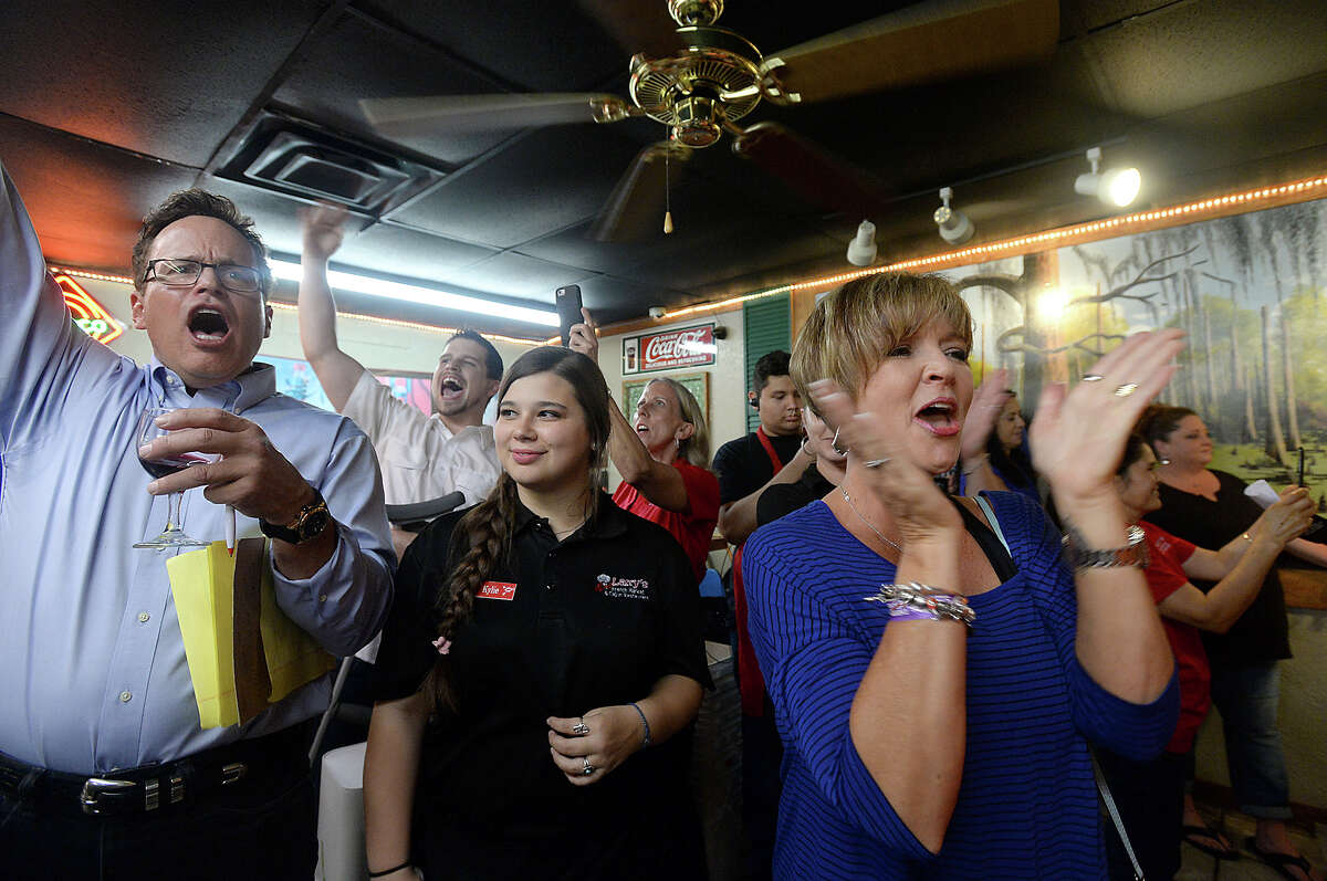 The crowd of spectateors, including contestant's wife Carla Derouen, cheers as the clock winds down to the finish during the crawfish eating contest Friday night at Larry's French Market in Groves. Contestants had 15 minutes to prove their crawfish consumption worth, vying for the grand prize of a Bayou Classic Crawfish Pot and burner or Bayou Classic 25-quart Ice Chest. Photo taken Friday, April 29, 2016 Kim Brent/The Enterprise
