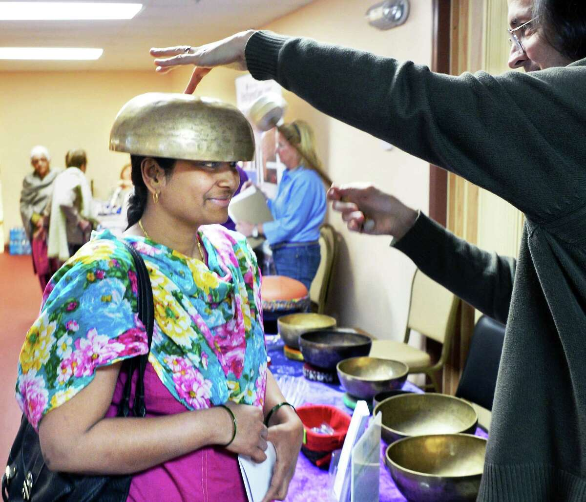 David Ciucevich administer sound meditation and healing to Rekha Jirankali, left, of Menands during the Hindu Cultural Center health fair Saturday April 30, 2016 in Colonie, NY. (John Carl D'Annibale / Times Union)