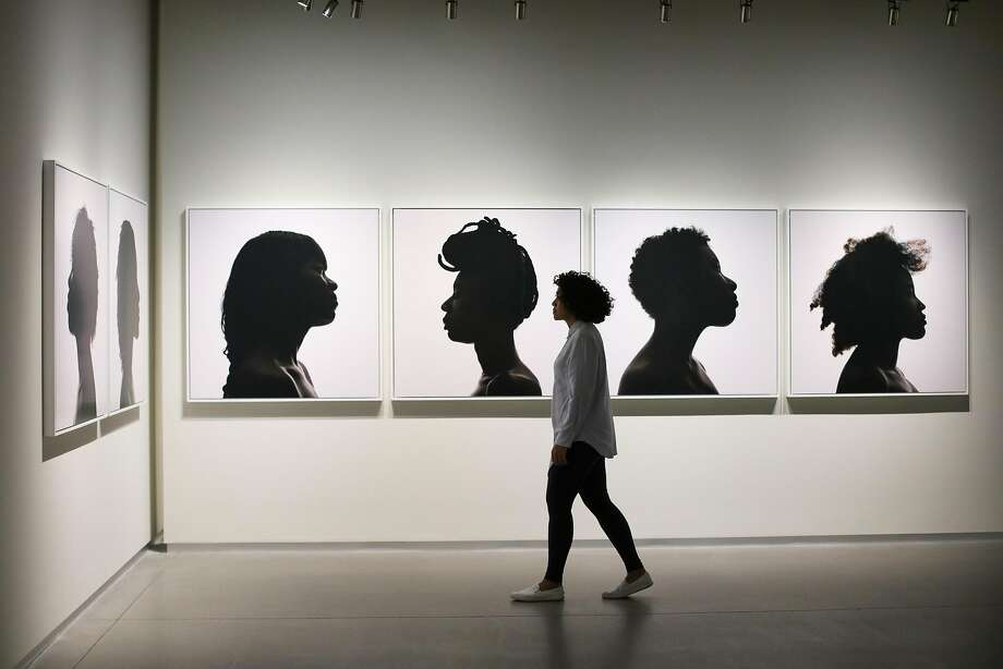 "Artist Erica Deeman walks past her photographs, which are in the show, ""Collected"", at Pier 24 Photography, in San Francisco, California, on Friday, April 29, 2016. Photo: Gabrielle Lurie, Special To The Chronicle"
