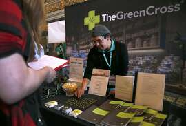 Michael Yannacone organizes his display for The Green Cross before Taylor Collins submits her resume at a cannabis industry job fair in San Francisco, Calif. on Saturday, April 30, 2016.