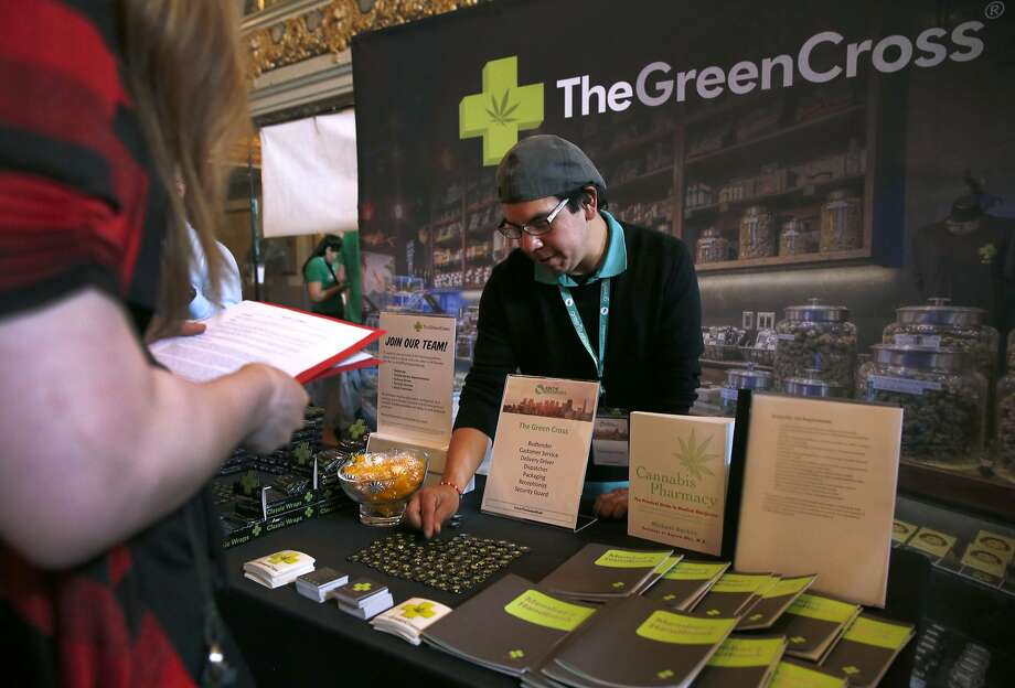 Michael Yannacone finishes his display for the Green Cross before Taylor Collins submits her resume at the pot job fair. Photo: Paul Chinn, The Chronicle