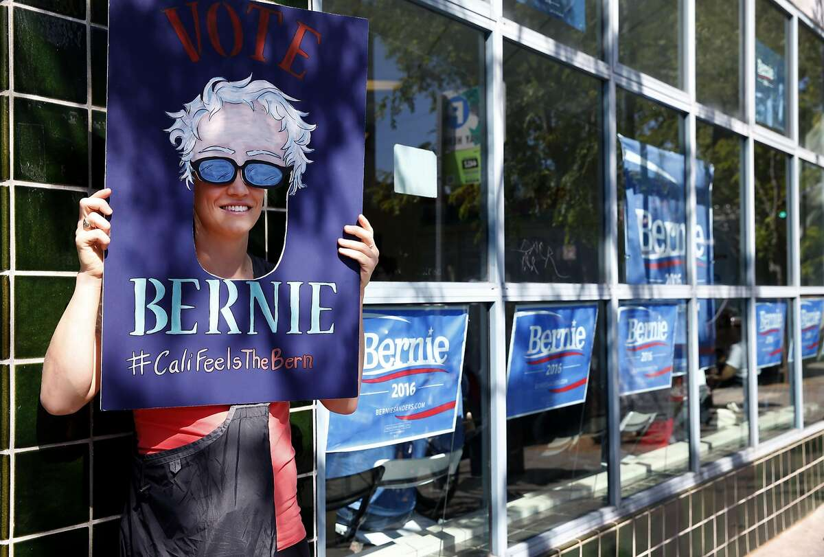 Kelly Blondin holds a mask for a photo taken by a friend at the opening of the Bay Area headquarters for the Bernie Sanders presidential campaign in Oakland, Calif. on Saturday, April 30, 2016.