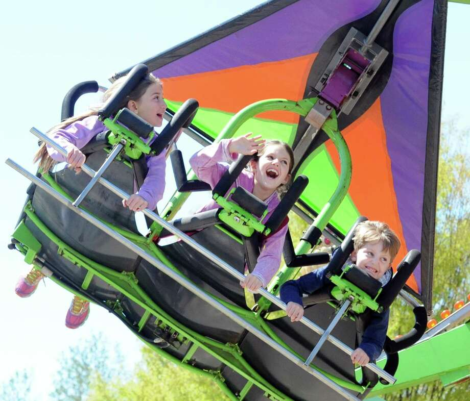 At center, Ava Jackson, 8, screams as her brother Alex Jackson, 6, right, smiles, as the pair rode the Fabulous Flyer ride at the North Mianus School Pow Wow at the school in the North Mianus section of Greenwich, Conn., Saturday, April 30, 2016. A springtime tradition since 1946, the festival/carnival is known for its many rides, a variety of food, games and live music. Karen Sherr, co-chair of the event, said money raised from the Pow Wow will go toward curriculum enrichment programs at the school. Photo: Bob Luckey Jr. / Hearst Connecticut Media / Greenwich Time