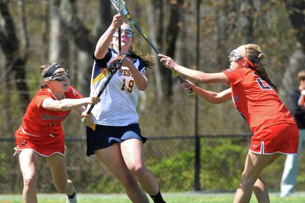 Weston's Grace Toner (19) tries to split Ridgefield's Kimberly Weinstock (2), right, and Ann Hage (26) in the girls lacrosse game between Ridgefield and Weston high schools, on Saturday morning, April 30, 2016, at Weston High School, Weston, Conn.