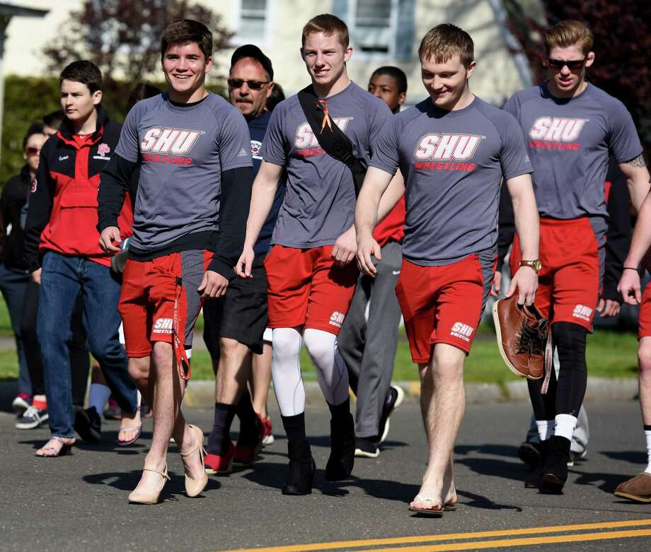 Sacred Heart University wrestlers Tim Johnson, Brandon Levesque and Alex Harnsberger, from left, march with their teammates in the Walk a Mile in Her Shoes event Saturday, April 30, 2016 in downtown Fairfield. The annual event sponsored by The Center for Family Justice raises money for the center and awareness about domestic violence. Photo: Autumn Driscoll / Hearst Connecticut Media / Connecticut Post freelance