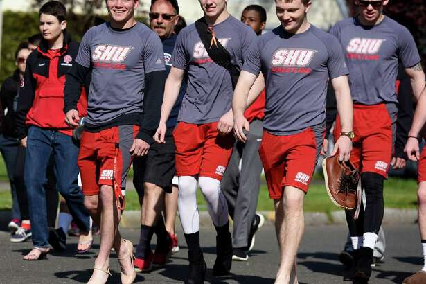 Sacred Heart University wrestlers Tim Johnson, Brandon Levesque and Alex Harnsberger, from left, march with their teammates in the Walk a Mile in Her Shoes event Saturday, April 30, 2016 in downtown Fairfield. The annual event sponsored by The Center for Family Justice raises money for the center and awareness about domestic violence.