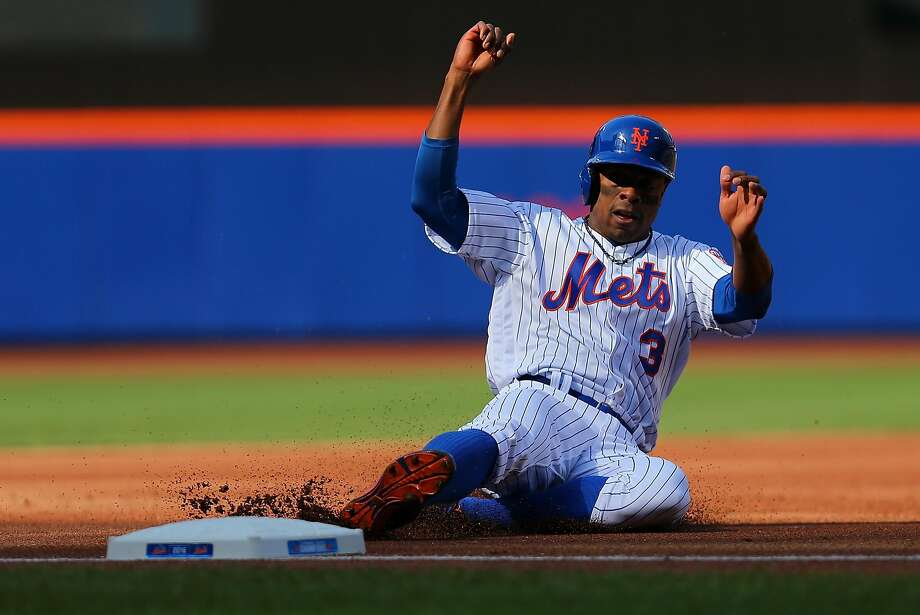 Curtis Granderson slides into third base on Michael Conforto's first-inning single. Photo: Mike Stobe, Getty Images
