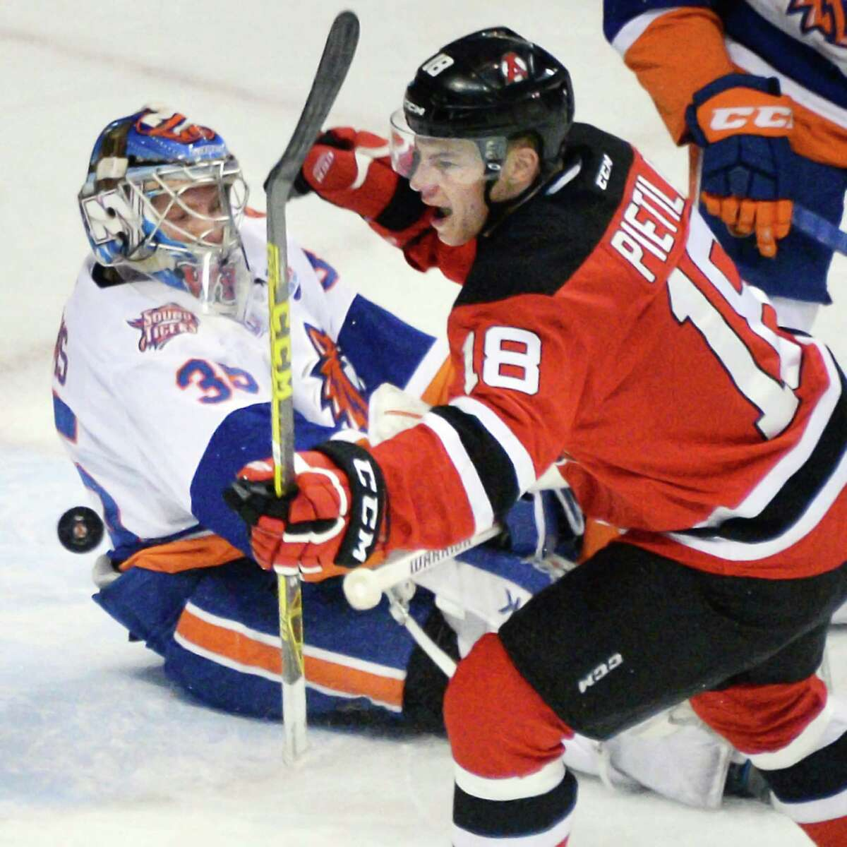 Albany Devils' #18 Blake Pietila reacts to scoring against Bridgeport Sound Tigers goalie Stephon Williams, left, during Saturday's game at the Times Union Center April 16, 2016 in Albany, NY. (John Carl D'Annibale / Times Union)