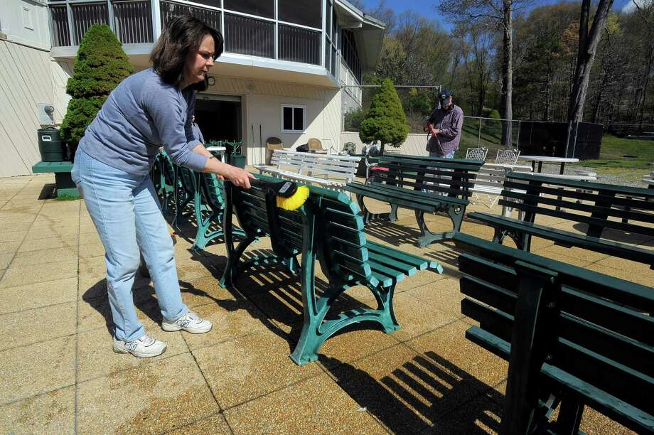 Sally Sluga, of Stamford, scrubs benches on Saturday at the Long Ridge Club. Sluga, who has been a member of the private swim and tennis club for six years, joined about 20 other members working on various projects around the club as they prepared for its season opening on Sunday. Photo: Matthew Brown / Hearst Connecticut Media / Stamford Advocate