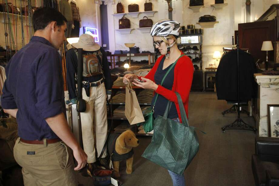 George Revel, 26, gives a same-day order to Greet Keustermans, a Postmates courier Oct. 22, 2014 in Revel's fly fishing store, Lost Coast Outfitters, in downtown San Francisco. Postmates is trying to diversify its deliveries beyond restaurant meals. Photo: Leah Millis, The Chronicle