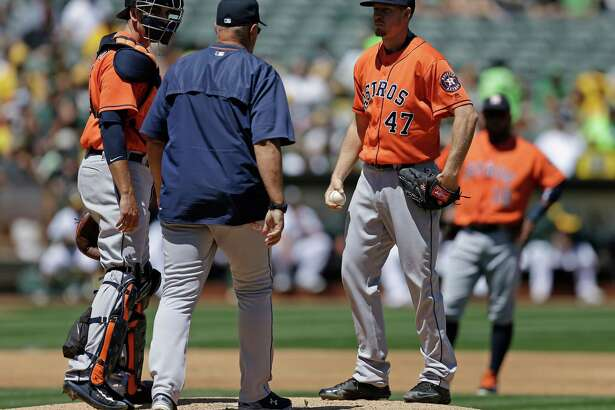 Houston Astros pitcher Chris Devenski (47) speaks with pitching coach Brent Strom in the second inning of a baseball game against the Oakland Athletics Saturday, April 30, 2016, in Oakland, Calif. (AP Photo/Ben Margot)