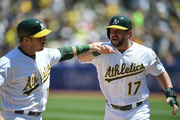 OAKLAND, CA - APRIL 30:  Josh Phegley #19 and Yonder Alonso #17 of the Oakland Athletics celebrates after they both scored against the Houston Astros in the bottom of the second inning at O.co Coliseum on April 30, 2016 in Oakland, California.