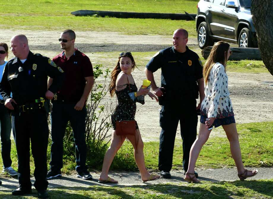 Fairfield police and private security guards watch as partygoers leave the Clam Jam on Saturday. Photo: Christian Abraham / Hearst Connecticut Media / Connecticut Post