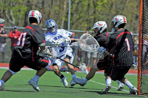 Darien Colin Minicus sneaks a shot past New Canaan goalie Drew Morris in a FCIAC boys lacrosse game at Darien High School on April 30, 2016. Darien defeated New Canaan 10-7.