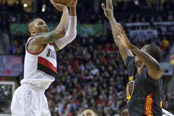 Portland Trail Blazers guard Damian Lillard, left, shoots over Golden State Warriors forward Harrison Barnes, right, during the second half of an NBA basketball game in Portland, Ore., Friday, Feb. 19, 2016. (AP Photo/Craig Mitchelldyer)