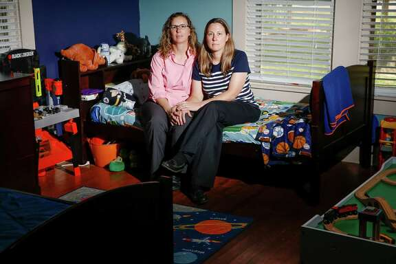 Foster parents Angela Sugarek, left, and Carol Jeffery sit Wednesday on the empty bed of the younger of their two foster children.