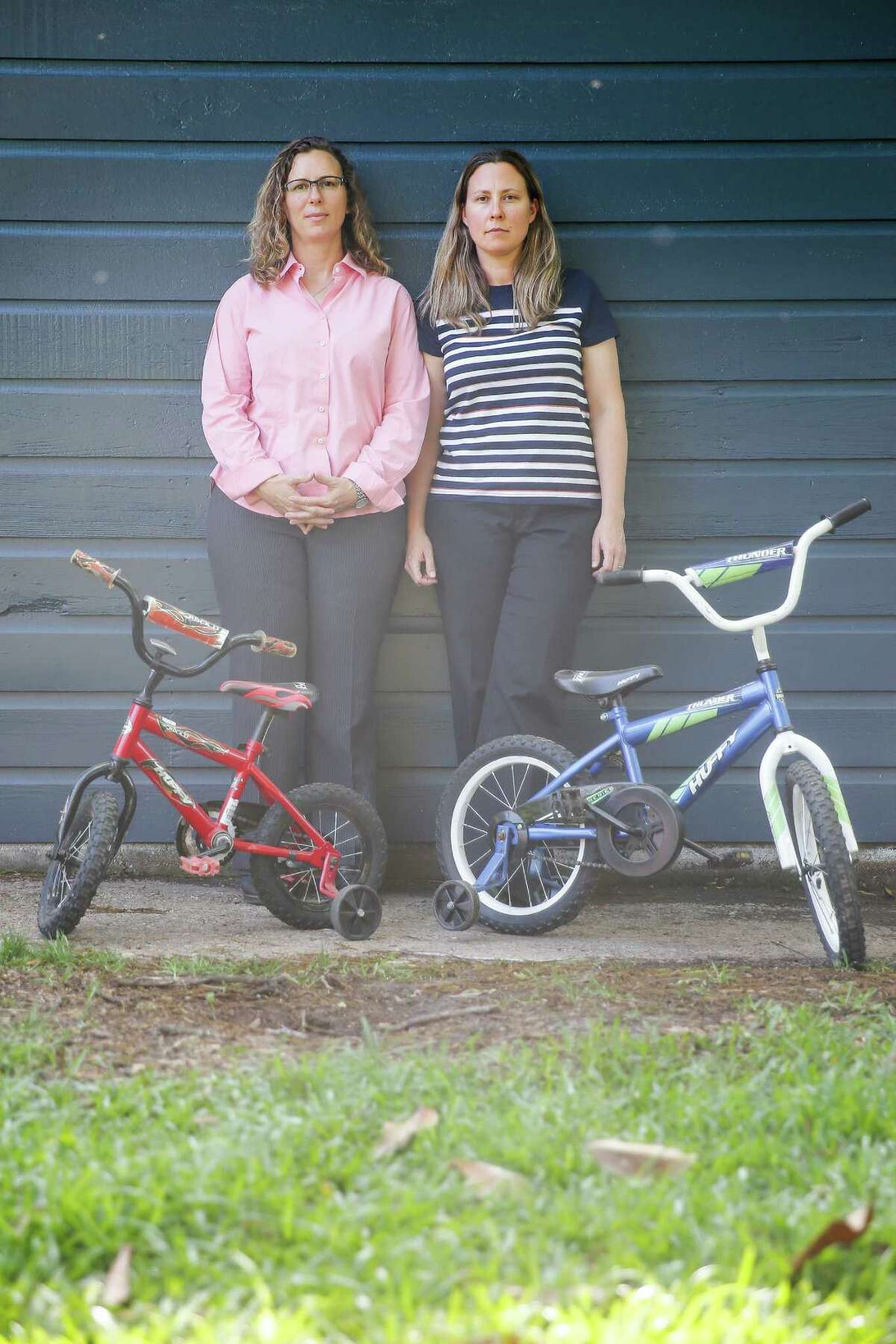 Foster parents Angela Sugarek, left, and Carol Jeffery stand next to the bikes they bought their two foster children Wednesday, April 27, 2016 in Houston. The couple had the two bothers, ages three and four, taken away from them by Child Protective Services after reporting that they believed the younger child was being abused by an older brother. ( Michael Ciaglo / Houston Chronicle )