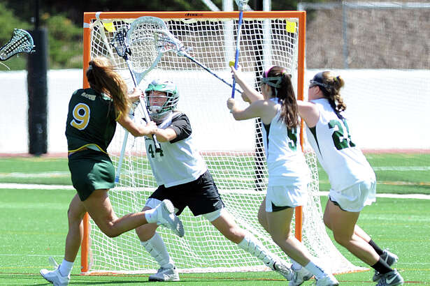 Greenwich Academy's Karina Schulze, left, scores a first-half goal past Sacred Heart goalie Maddie McLane while being defended by Sacred Heart's Emily Micciulli, 9, and Ellen Purcel at Greenwich Academy on Saturday. Schulze scored five goals and Greenwich Academy won 12-9.