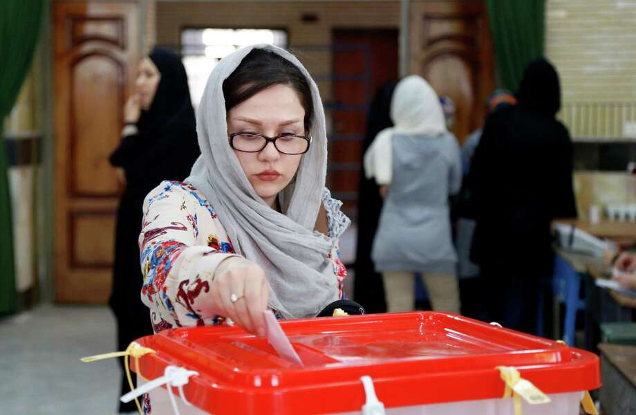 An Iranian woman casts her ballot Friday in the parliamentary runoff elections. Photo: STR / AP