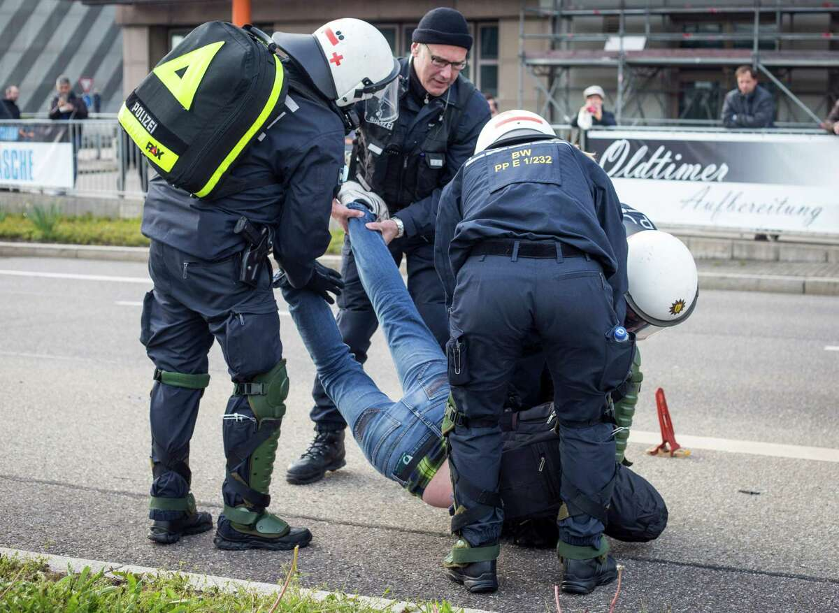 Police detain a leftist demonstrator on the occasion of a party convention of the Alternative for Germany, or AfD, in Stuttgart, Germany Saturday, April 30, 2016. (Christoph Schmidt/dpa via AP) ORG XMIT: LGL102