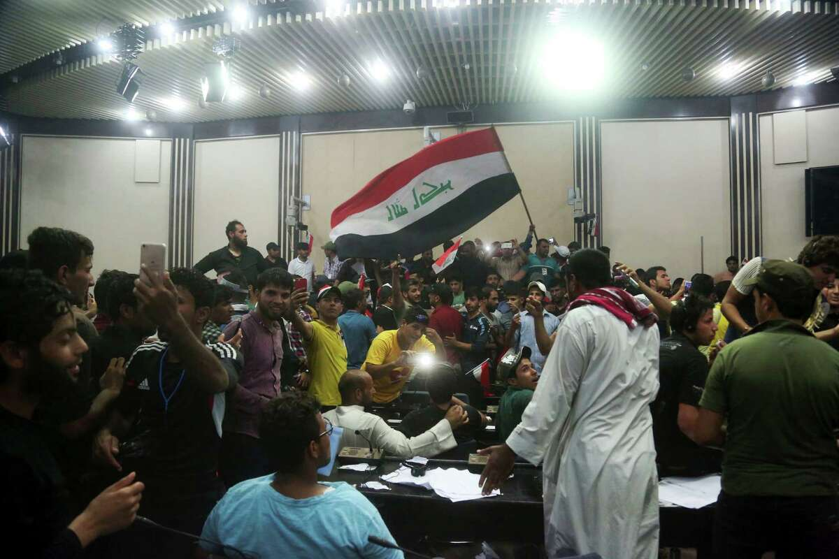 Supporters of Shiite cleric Muqtada al-Sadr storm parliament in Baghdad's Green Zone, Saturday, April 30, 2016. Dozens of protesters climbed over the blast walls and could be seen storming the Parliament building, carrying Iraqi flags and chanting against the government. (AP Photo/Khalid Mohammed) ORG XMIT: BKM101