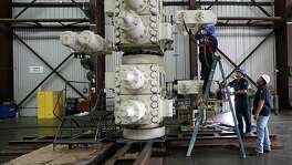 GE Oil & Gas employees work on a blowout preventer last week at GE's manufacturing facility. The firm is waiting to deploy the last blowout preventer it has because of the oil downturn.