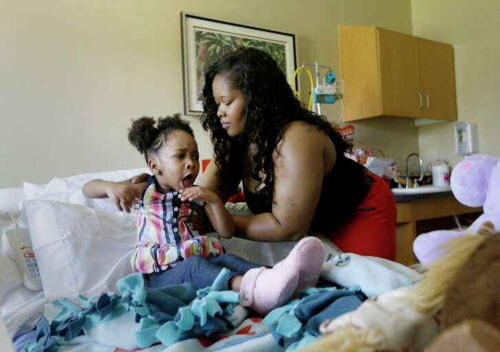 Courissa Hall, right, helps position her daughter Nevaeh, 4, in her bed at a specialty and rehabilitation hospital in west Houston Thursday, April 7, 2016, in Houston. Nevaeh suffered brain damage during a dental procedure.