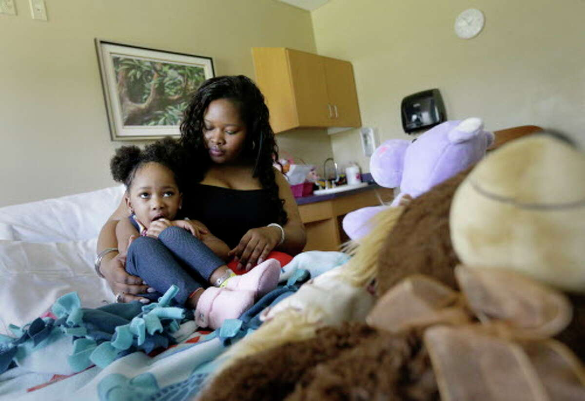 Courissa Hall, right, poses for a portrait with her daughter Nevaeh, 4, at a specialty and rehabilitation hospital in west Houston Thursday, April 7, 2016, in Houston. Nevaeh suffered brain damage during a dental procedure.