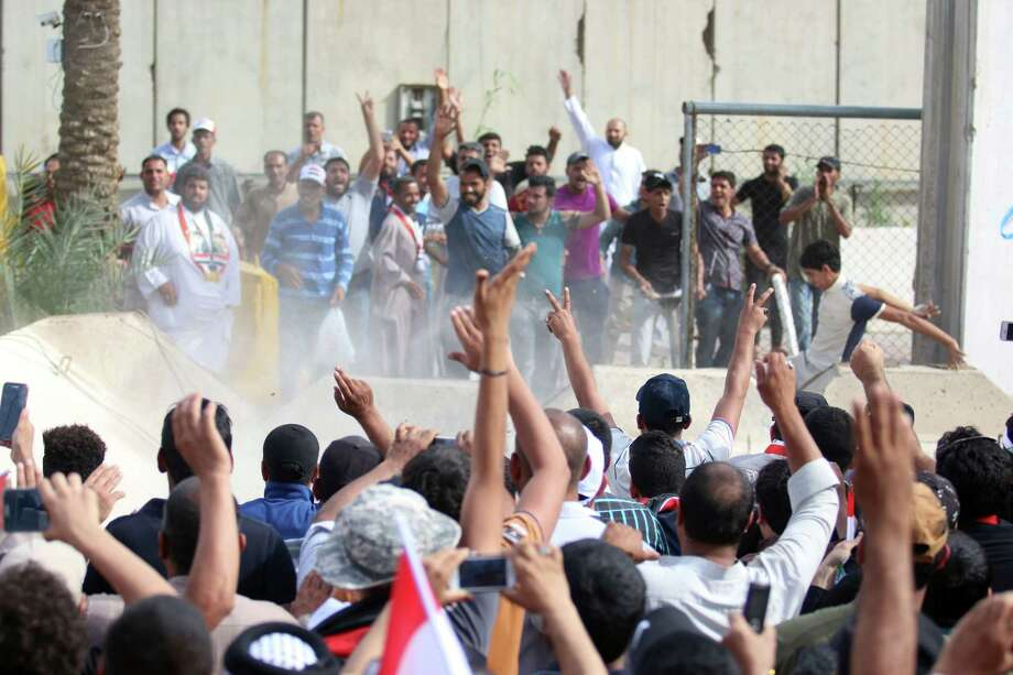 """Iraqi protesters celebrate as they breach a concrete wall surrounding the parliament after breaking into Baghdad's fortified """"Green Zone"""" on Saturday.   Photo: HAIDAR MOHAMMED ALI, Stringer / AFP or licensors"""