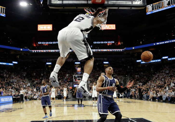 San Antonio Spurs forward Kawhi Leonard (2) scores over Oklahoma City Thunder guard Russell Westbrook (0) during the first half in Game 1 of a second-round NBA basketball playoff series, Saturday, April 30, 2016, in San Antonio. (AP Photo/Eric Gay)   Spurs vs. Thunder NBA playoffs Game 1.