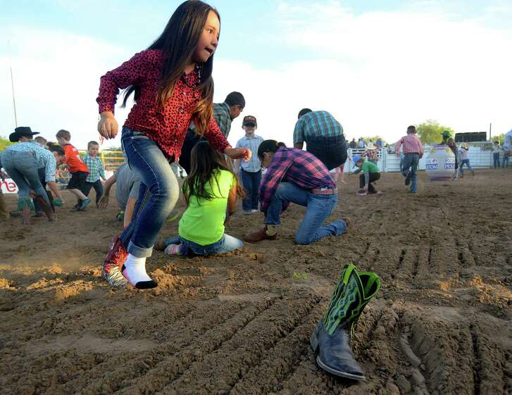 Children participate in a race for their boots and shoes during the Bullnanza event at the Dimmit County Fairgrounds in Carrizo Springs, Texas, on Saturday, April 30, 2016.