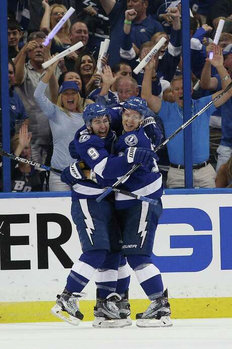 Tyler Johnson, left, celebrates with teammate Ondrej Palat and the Lightning's fans after Johnson scored the first of his two goals in Saturday night's 4-1 victory over the New York Islanders at Tampa, Fla. Photo: Scott Iskowitz, Stringer / 2016 Getty Images