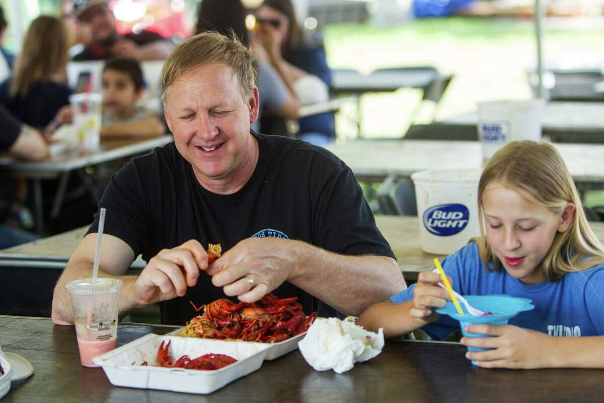 Mark Smith and Bailey Smith, of Cypress, eat a batch of crawfish during the Texas Crawfish and Music Festival on Saturday, April 30, 2016, in Spring.