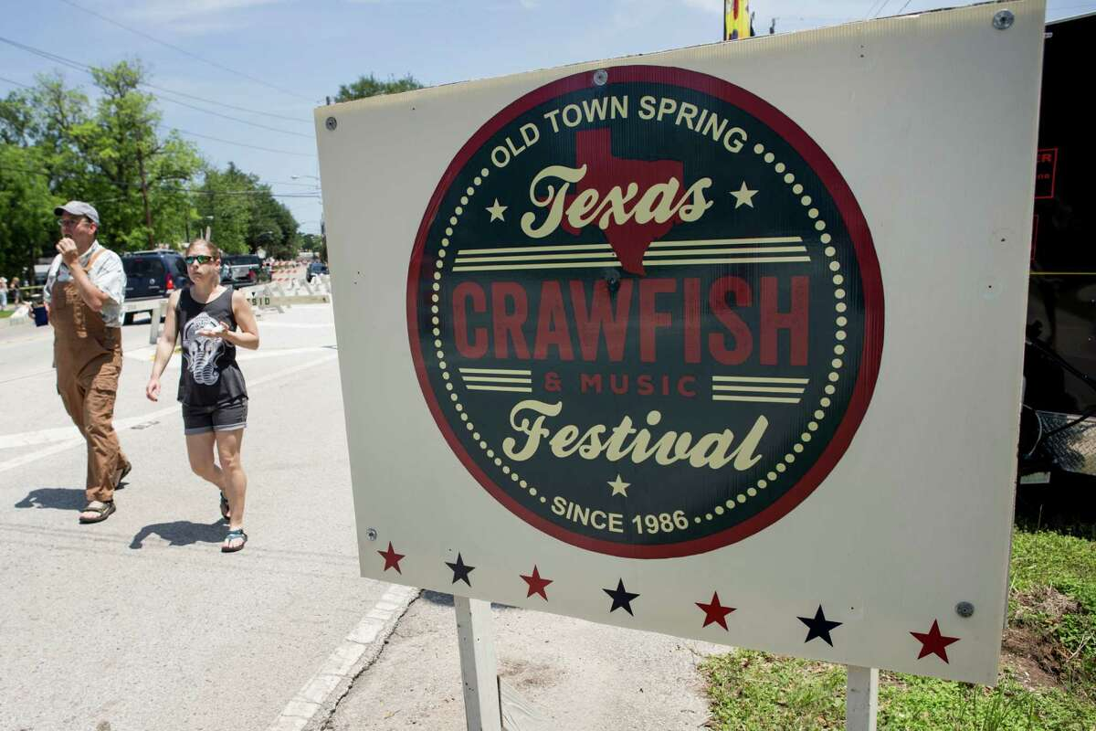 Visitors to the Texas Crawfish and Music Festival walk past the entrance sign on Saturday, April 30, 2016, in Spring.