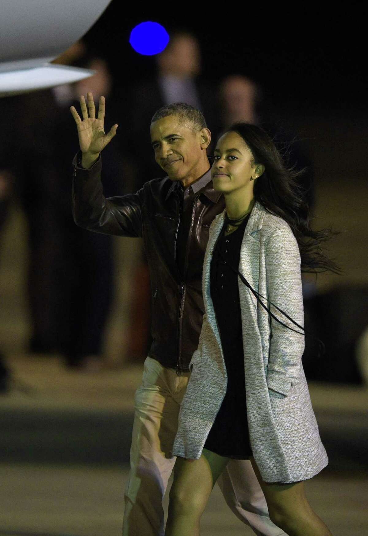 US President Barack Obama waves next to his daughter Malia before boarding the Air Force One and head back to United States, at Ministro Pistarini International Airport in Ezeiza, Buenos Aires, Argentina on March 25, 2016. AFP PHOTO / JUAN MABROMATAJUAN MABROMATA/AFP/Getty Images