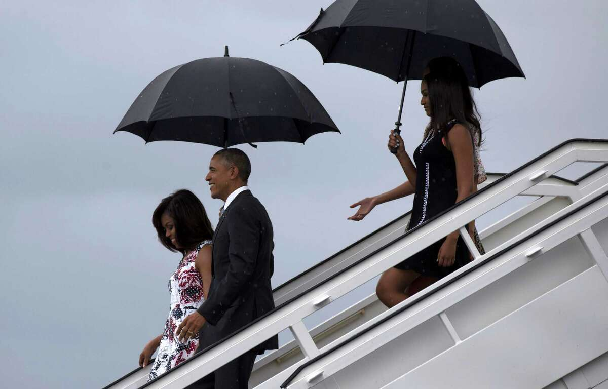 President Barack Obama, second from left, arrives with first lady Michelle Obama, left, and their daughters Sasha, front right, and Malia, as they exit Air Force One at the airport in Havana, Cuba, Sunday, March 20, 2016. Obama and his family are traveling to Cuba, the first U.S. president to visit the island in nearly 90 years. (Cubadebate/Ismael Francisco via AP) ORG XMIT: CUB102