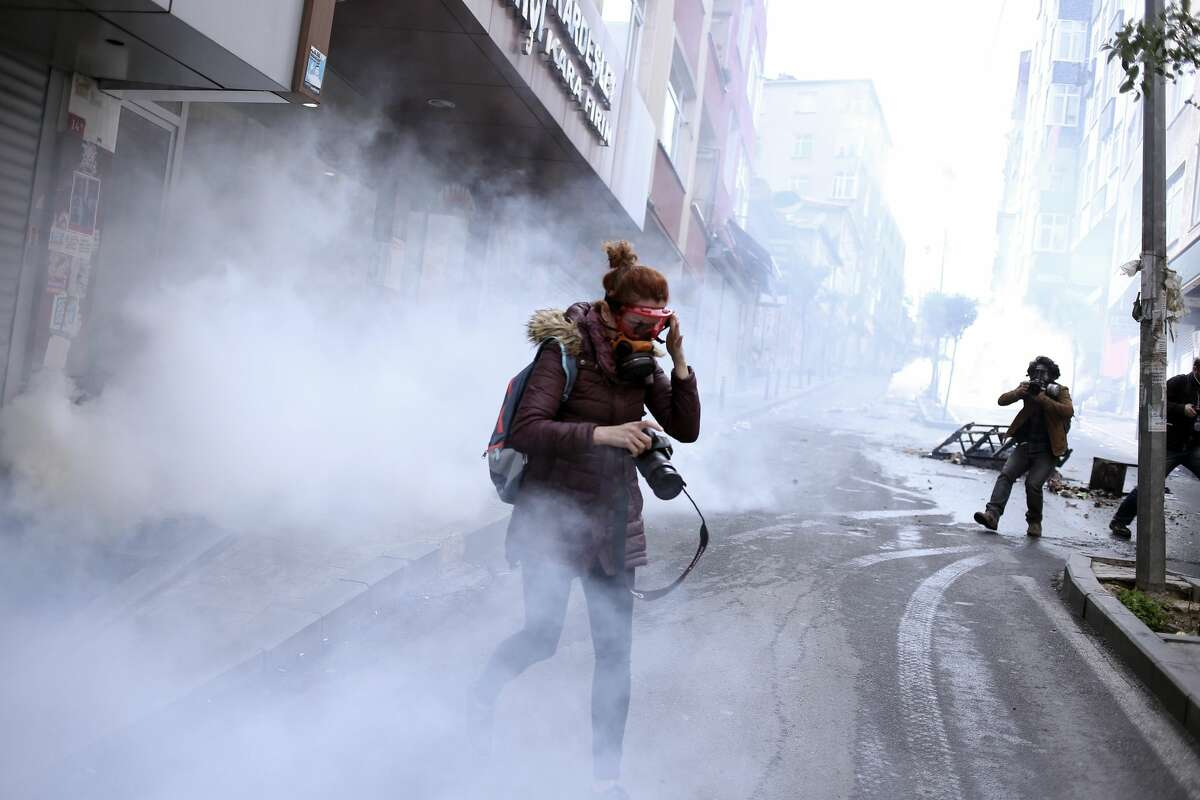 A woman covers her face as leftist demonstrators clash with riot police using tear gas to disperse them during May Day celebrations in Istanbul, Sunday, May 1, 2016. Security forces prevented leftist groups trying to reach city's iconic Taksim Square to celebrate May Day.(AP Photo/Cagdas Erdogan)