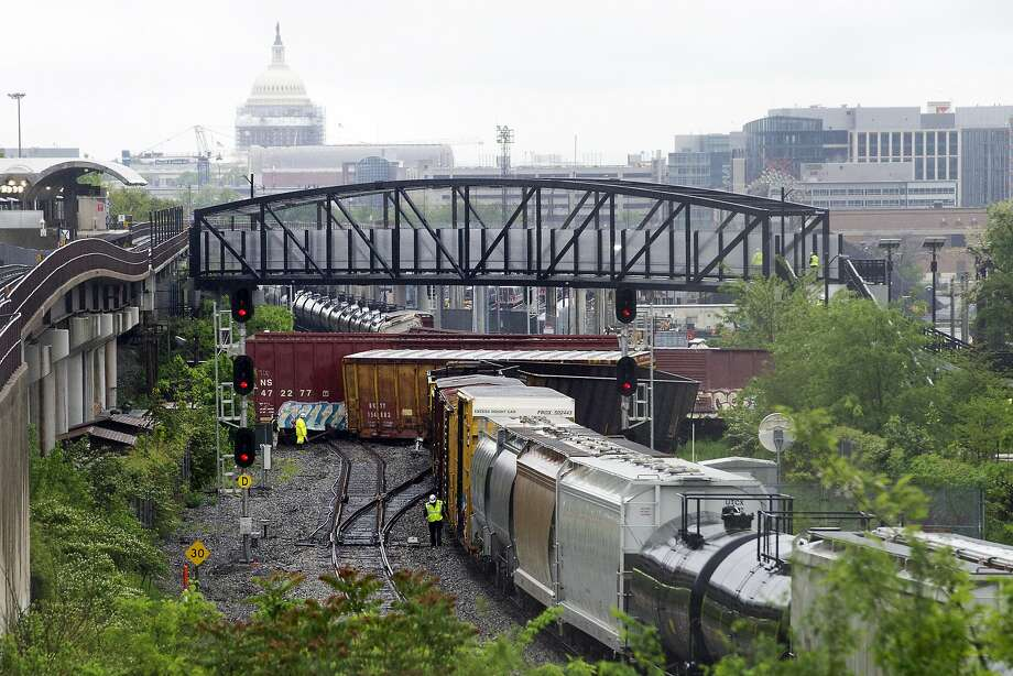 Several cars overturned after a CSX freight train derailed in Washington, D.C. The Capitol is seen in the background. Photo: Cliff Owen, Associated Press