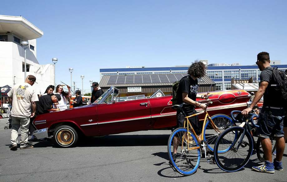 Bicyclists hang out next to a lowrider being checked in during the Give Something Back Car Show in San Francisco. Photo: Connor Radnovich, The Chronicle