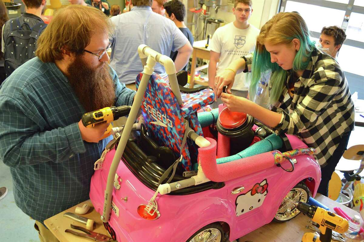 Ben Merkel, left, a tech education major at Central Connecticut State University, and Alex Glynn, 16, a Darien High School junior, put the finishing touches on a car.