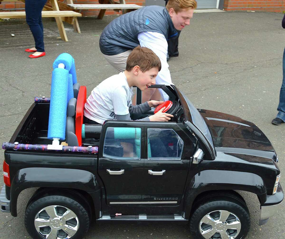 Chase Sadowski, 9, of North Salem, N.Y., takes his first ride in a car, assisted by Darien student Sam Giorgio, 17.