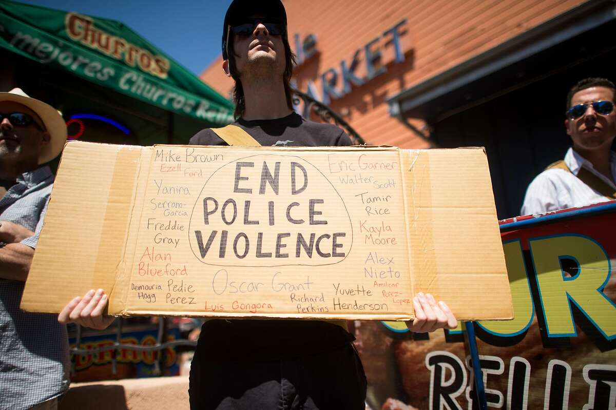 Mike Martin holds a sign against police violence during a May Day rally supporting workers rights in Oakland, Calif., on Sunday, May 1, 2016.