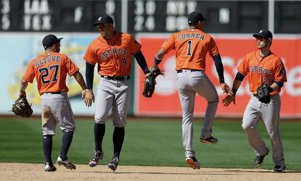 From left, Houston Astros Jose Altuve, George Springer, Carlos Correa, and Preston Tucker celebrate the 2-1 victory over the Oakland Athletics at the end of a baseball game Sunday, May 1, 2016, in Oakland, Calif. (AP Photo/Ben Margot)