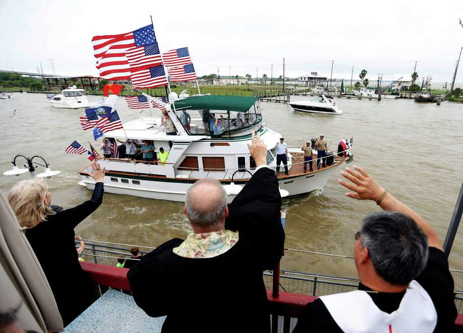 "Pastor Jack Matkin, of Dickinson First United Methodist Church, left, and Rev. Carlos De La Torre, St. Alphonsus, bless a decorated boat as it passed by during the 48th annual Blessing of the Fleet, on the Kemah Boardwalk, Sunday, May 1, 2016, in Kemah. The Blessing of the Fleet ceremony, with this year's theme of ""Go Texas"", is a celebration of the local shrimping culture for a safe and bountiful season, put on by the Clear Lake Elks Lodge and Kemah Boardwalk. Photo: Karen Warren, Houston Chronicle / © 2016 Houston Chronicle"
