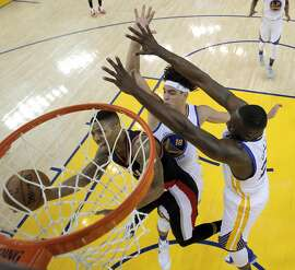 Damian Lillard (0) shoots while defended by Anderson Verajao (18), and Draymond Green (23) in the first half as the Golden State Warriors played the Portland Trail Blazers at Oracle Arena in Oakland , Calif., on Monday, April 25, 2016., Calif., on Sunday, May 1, 2016.