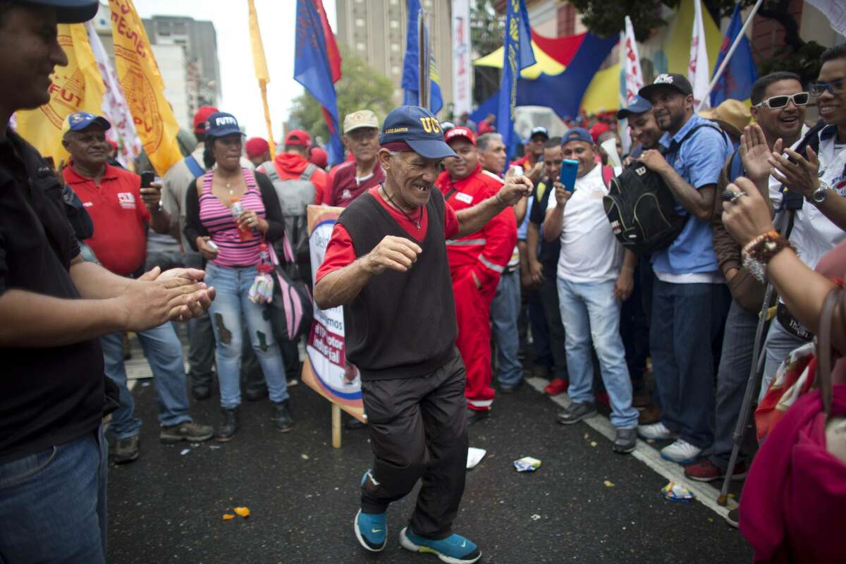 A government supporter dances during a May Day march in Caracas, Venezuela, Sunday, May 1, 2016. President Maduro ordered a 30 percent increase in the minimum wage, the latest move by the socialist government to grapple with high inflation and economic stagnation. (AP Photo/Ariana Cubillos)
