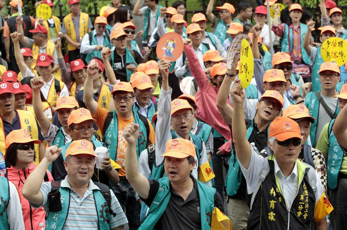 Taiwanese workers shout slogans during a May Day rally in Taipei, Taiwan, Sunday, May 1, 2016. Thousands of protesters from different labor groups protest on the street to ask for raising minimum wage and shorter working hours. (AP Photo/Chiang Ying-ying)