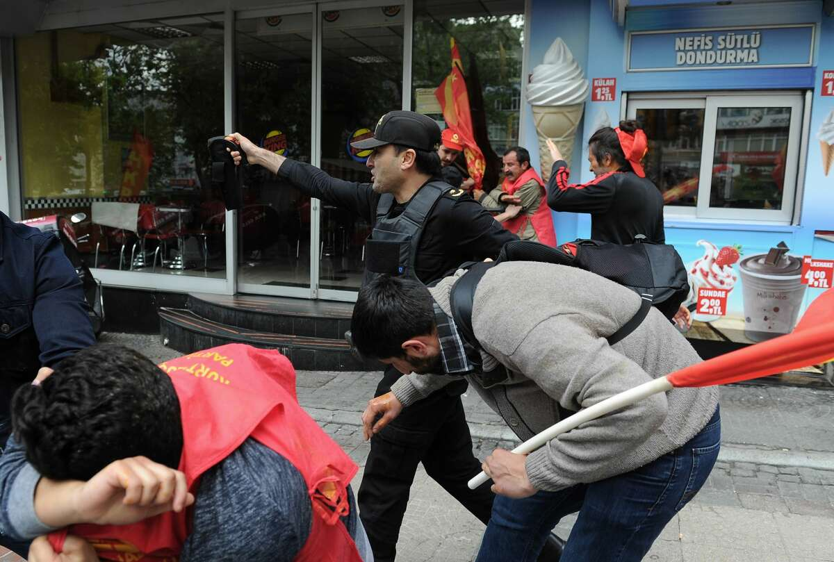 Police officers detain demonstrators, in Istanbul, Turkey, Sunday, May 1, 2016. Turkish police on Sunday prevented a small group of May Day demonstrators from reaching Istanbul?'s iconic Taksim Square. Security forces started to detain some of the 15 people in an effort to prevent their march. (AP Photo/Omer Kuscu)