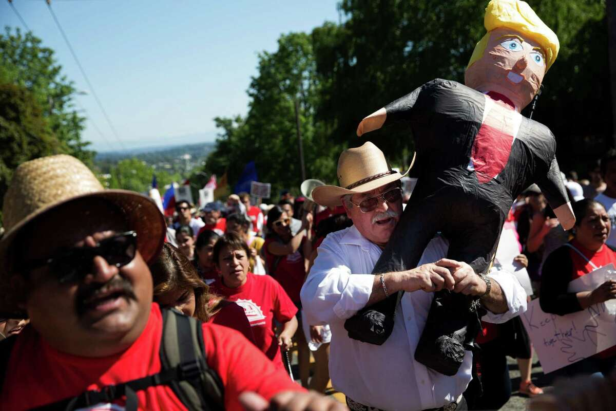 Marcos Angelos carries a Donald Trump pinata during the annual May Day immigration and workers rights march from Judkins Park to the federal courthouse downtown, May 1, 2016.