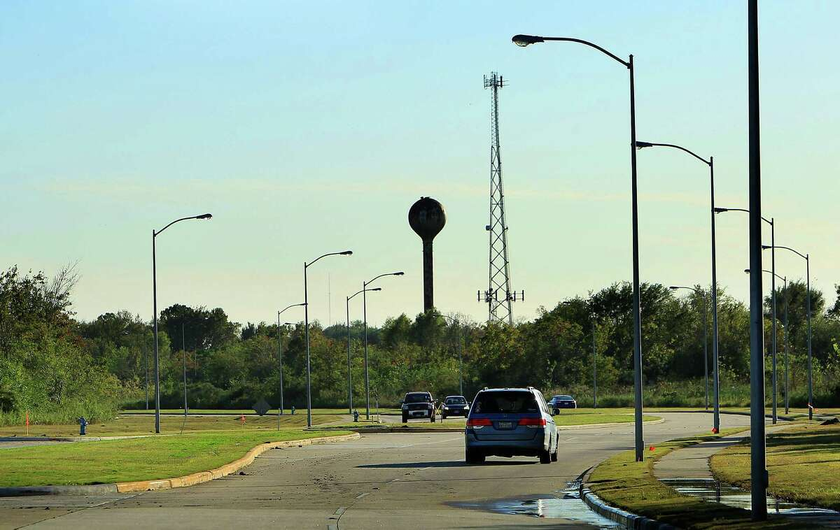 Cars drive along Willowbend Boulevard, which cuts through the center of a 300-acre swath of land where UT plans to build an